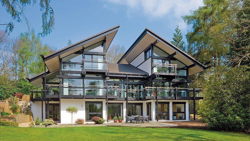 Bauen mit Glas - Ein Haus mit Bäumen im Hintergrund - Huf Haus