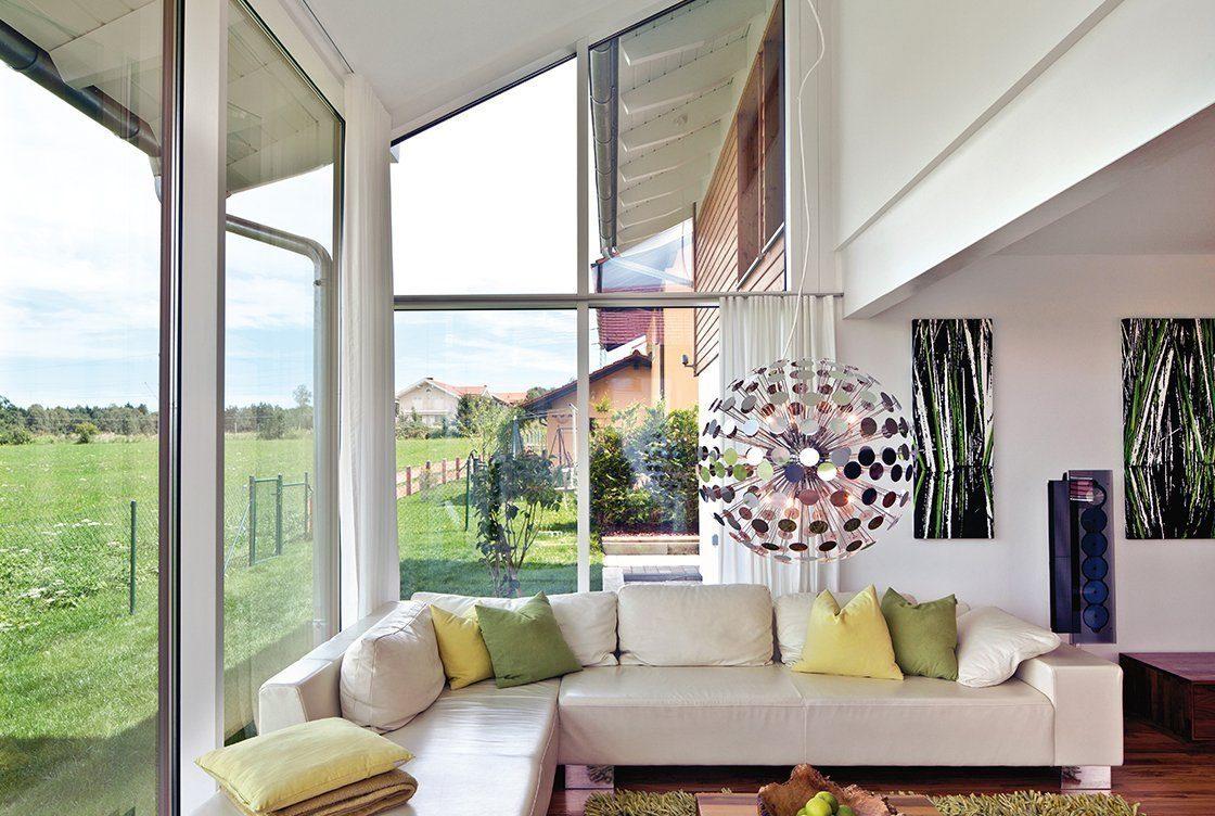 Vitalhaus Seehausen - Ein Wohnzimmer mit Möbeln und einem großen Fenster - Regnauer Fertigbau GmbH & Co. KG