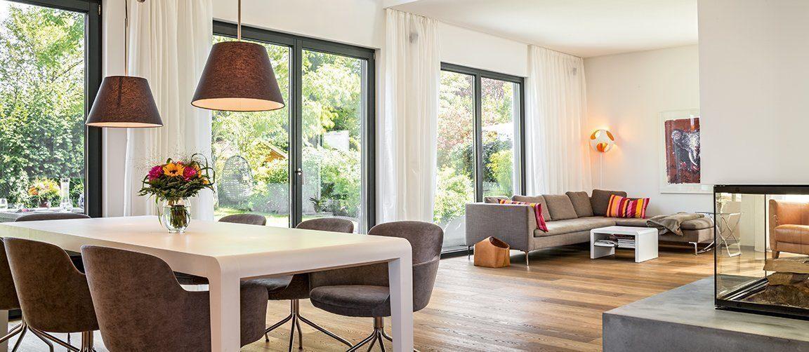 Vitalhaus München - Eine Ansicht eines mit Möbeln gefüllten Wohnzimmers und eines großen Fensters - Regnauer Fertigbau GmbH & Co. KG