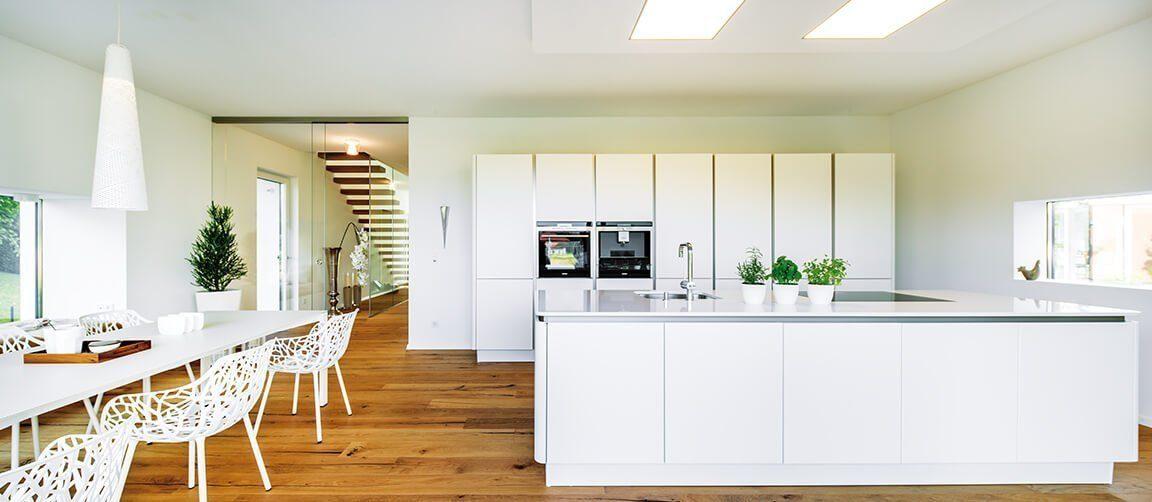 Musterhaus Ambienti+ - Eine Küche mit weißen Schränken und einem Esstisch - Regnauer Fertigbau GmbH & Co. KG