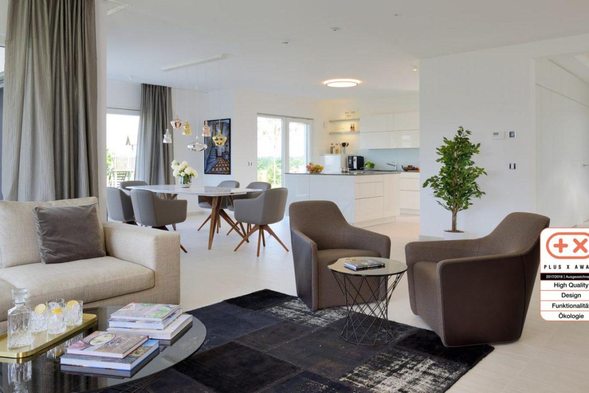 Musterhaus Bungalow Vita - Ein Wohnzimmer mit Möbeln und einem großen Fenster - Fertighaus Weiss