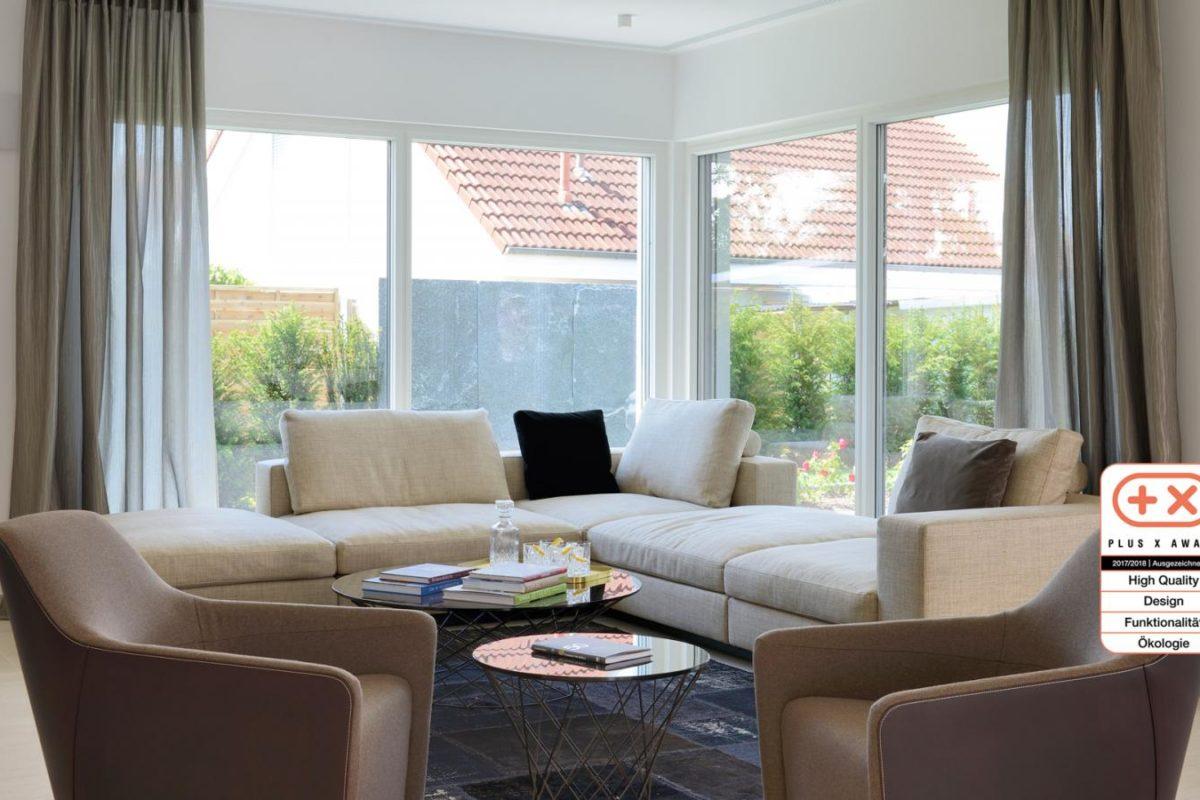 Musterhaus Bungalow Vita - Eine Ansicht eines mit Möbeln gefüllten Wohnzimmers und eines großen Fensters - Fertighaus Weiss