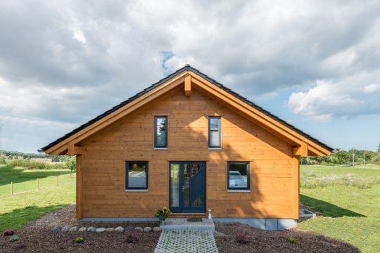 Musterhaus Wismarbucht - Ein großes Backsteingebäude mit Gras vor einem Haus - Haus