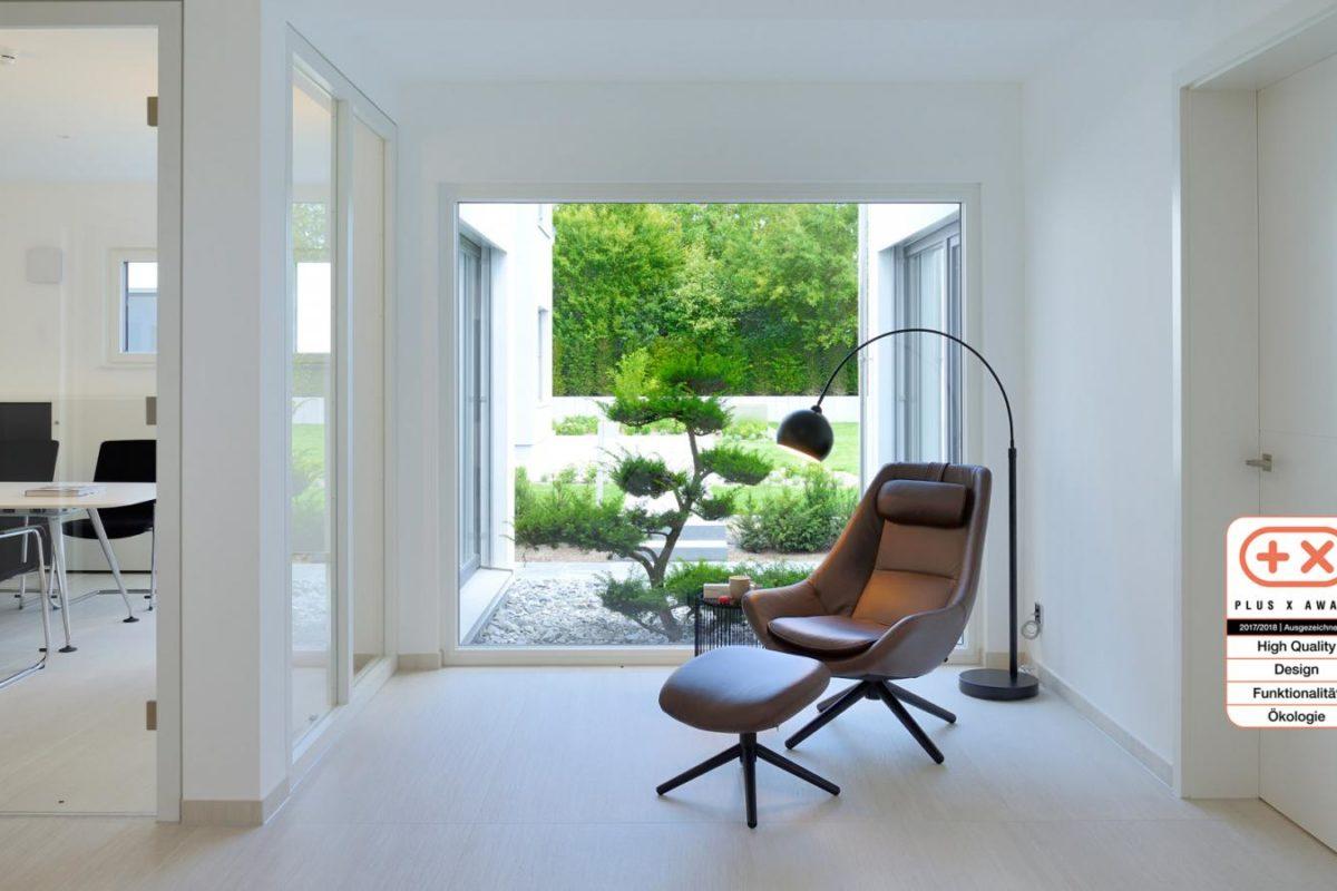 Musterhaus Bungalow Vita - Eine Ansicht eines mit Möbeln gefüllten Wohnzimmers und eines großen Fensters - Interior Design Services