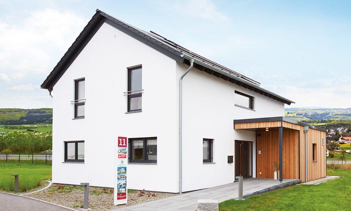 Musterhaus Günzburg - Ein großes Backsteingebäude mit Gras vor einem Haus - Haus