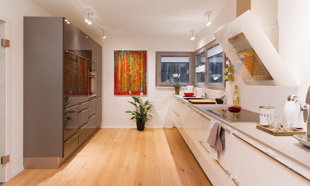 Musterhaus Köln - Eine Küche mit einer Insel mitten in einem Raum - Interior Design Services