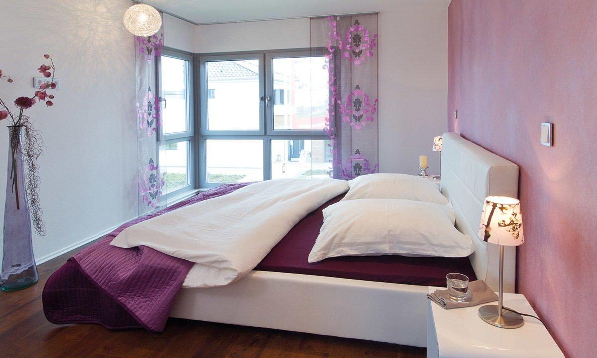 Musterhaus Köln - Ein Schlafzimmer mit einer rosa Decke - Schlafzimmer