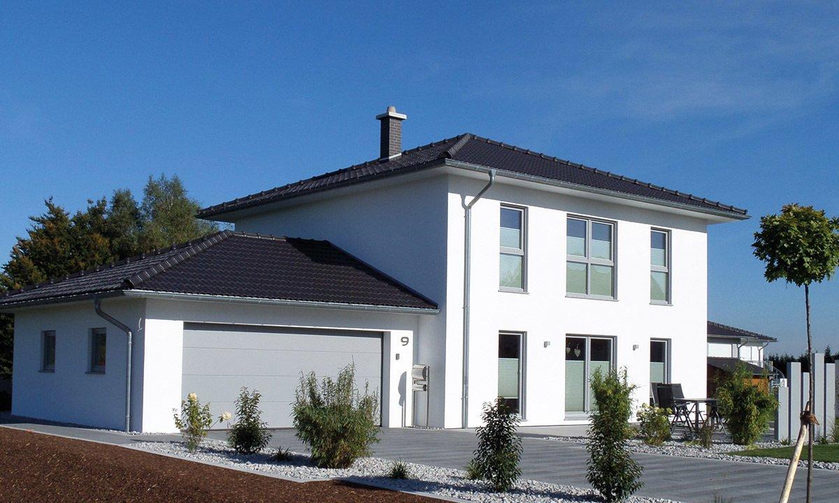 Medio - Ein Haus mit Bäumen vor einem Gebäude - Fingerhut Haus GmbH & Co. KG