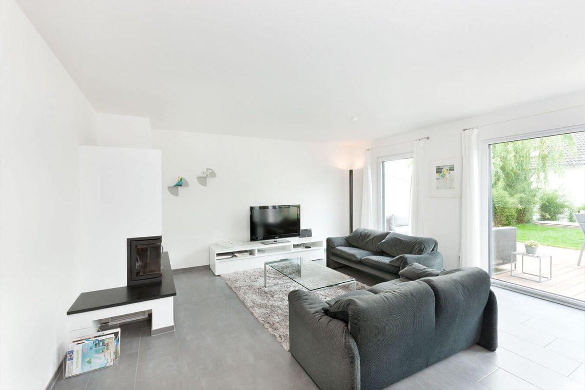 Haus U 089 - Ein Wohnzimmer mit Möbeln und einem großen Fenster - Wohnzimmer