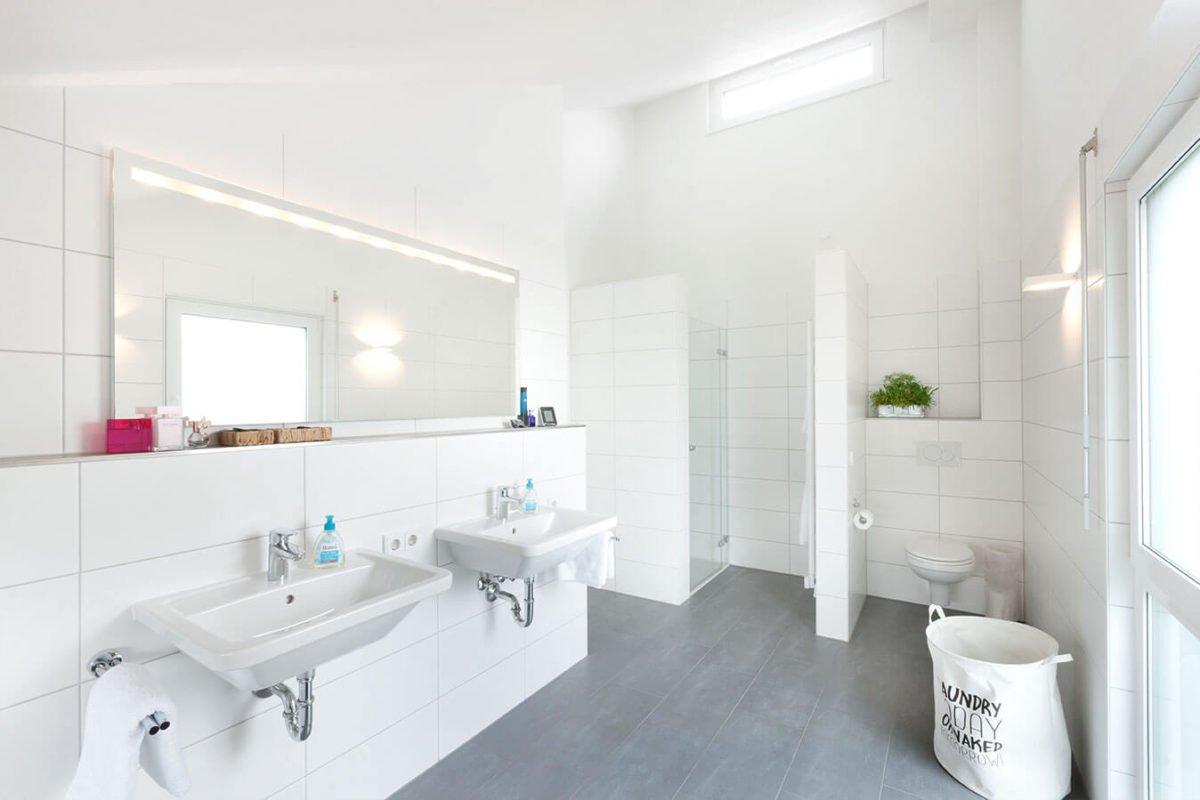 Haus U 089 - Eine weiße Spüle sitzt unter einem Spiegel - Bad