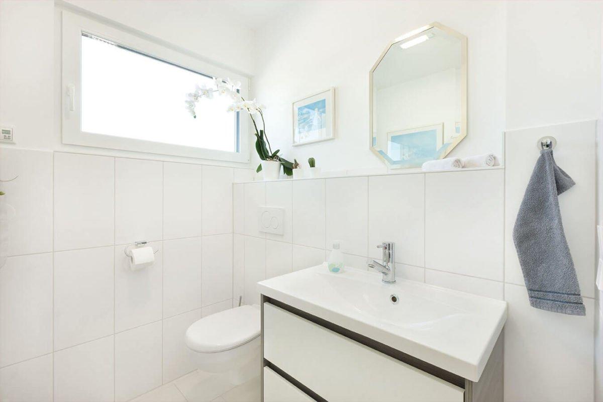 Haus U140 - Eine weiße Spüle sitzt unter einem Spiegel - Bad