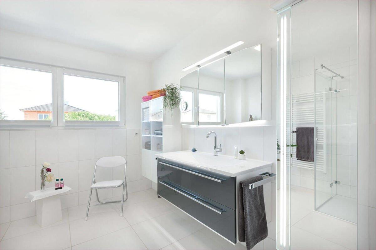 Haus U140 - Ein weißes Waschbecken sitzt unter einem Fenster - Interior Design Services