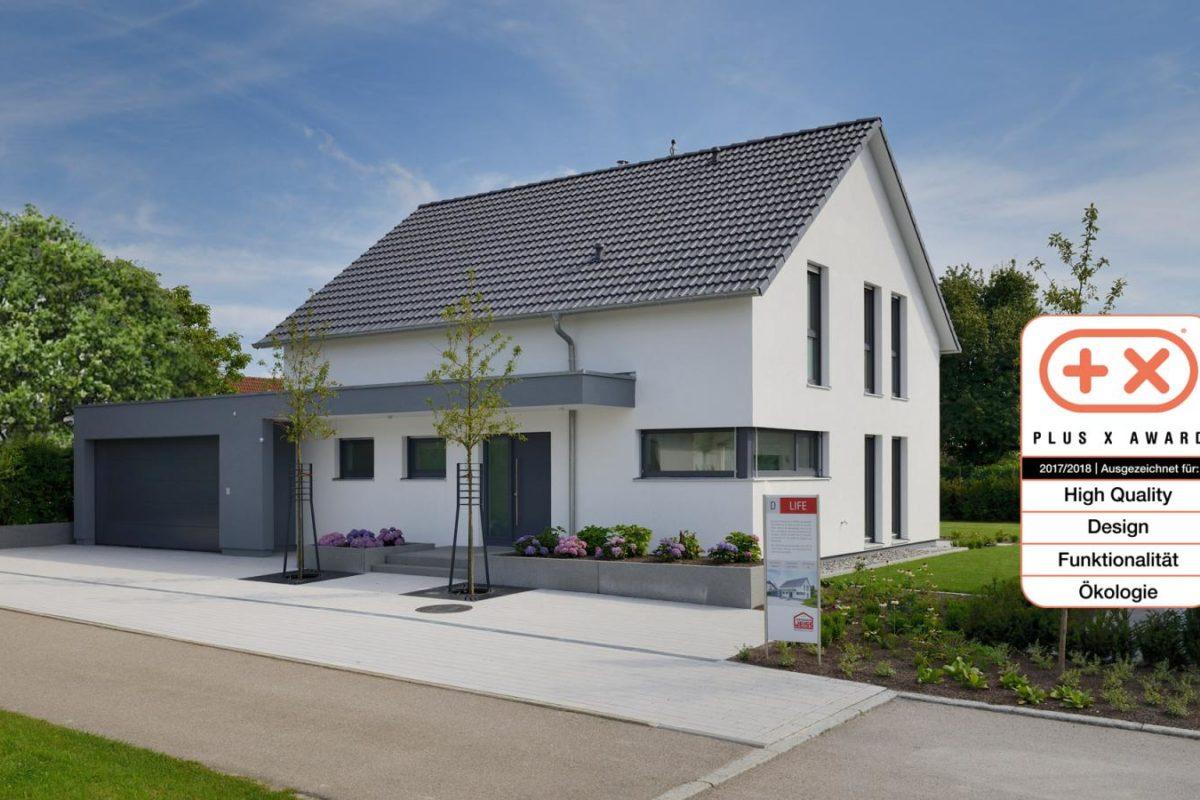 Musterhaus Life - Ein Haus mit einem Schild am Straßenrand - Fertighaus Weiss