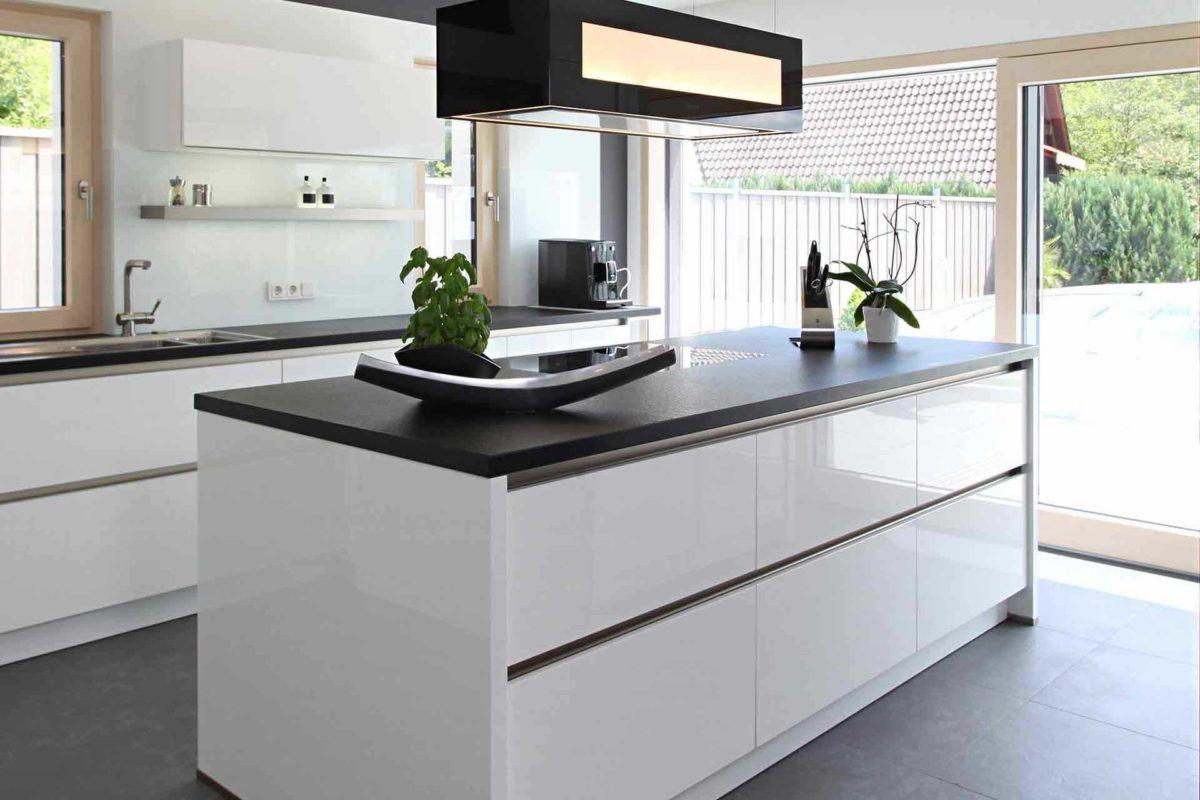Stadtvilla Riederle - Eine moderne Küche mit weißen Schränken und einem Fenster - Küche
