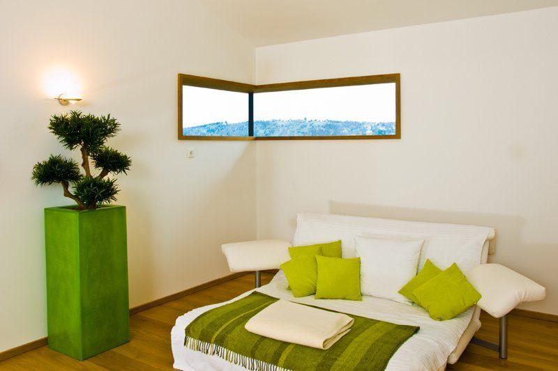Klassischer Bungalow - Ein Schlafzimmer mit einem Bett und einem Stuhl in einem Raum - Bungalow