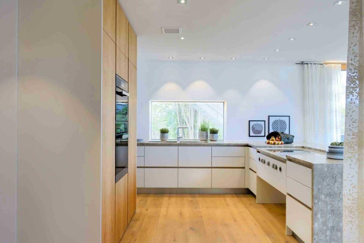 Haus am See - Eine Küche mit weißen Schränken - Küche