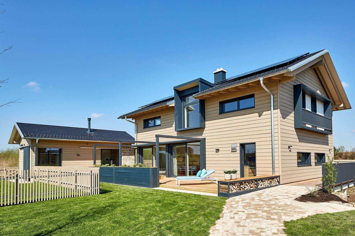 Musterhaus Heimat 4.0 - Ein großes Backsteingebäude mit Gras vor einem Haus - Bau-Fritz GmbH & Co. KG, seit 1896