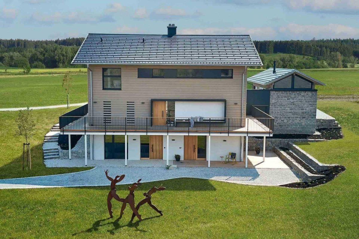 Musterhaus Heimat 4.0 - Eine große Wiese vor einem Gebäude - Holzhaus