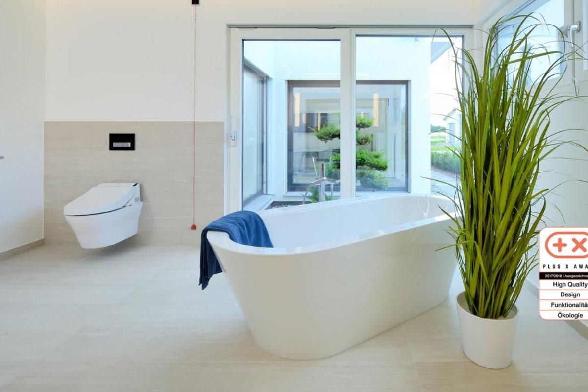 Musterhaus Bungalow Vita - Eine große weiße Wanne sitzt neben einem Fenster - Design
