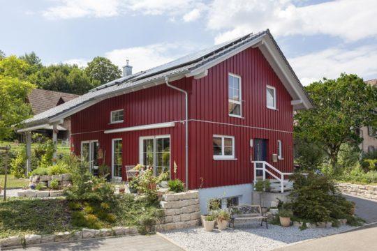 Haus Hälker - Ein Haus mit Büschen vor einem Backsteingebäude - SchwörerHaus KG Musterhaus Poing