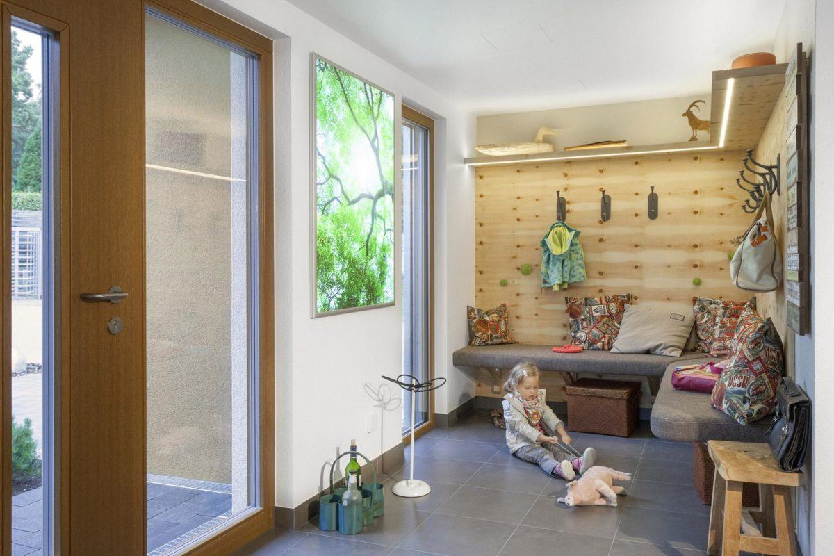Schwörer Haus Musterhaus Villingen-Schwenningen - Ein Wohnzimmer mit Möbeln und Blumenvase am Fenster - SchwörerHaus KG Musterhaus Villingen-Schwenningen