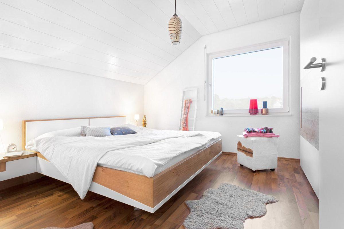 Haus Noller - Ein Schlafzimmer mit einem Bett und einem Schreibtisch in einem Raum - SchworerHaus KG