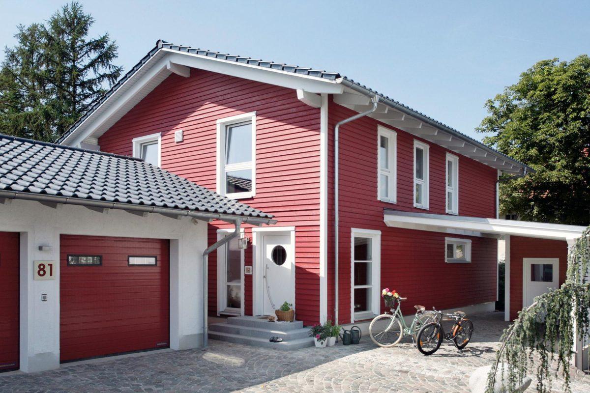 Plan E 15-143.1 - Ein Haus, das vor einem Backsteingebäude geparkt ist - Fertighaus
