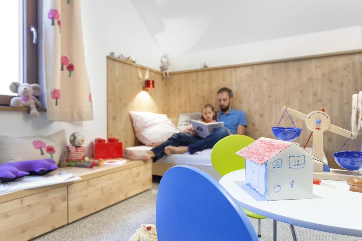 Schwörer Haus Musterhaus Villingen-Schwenningen - Eine Person, die auf einem Bett sitzt - Kinderzimmer