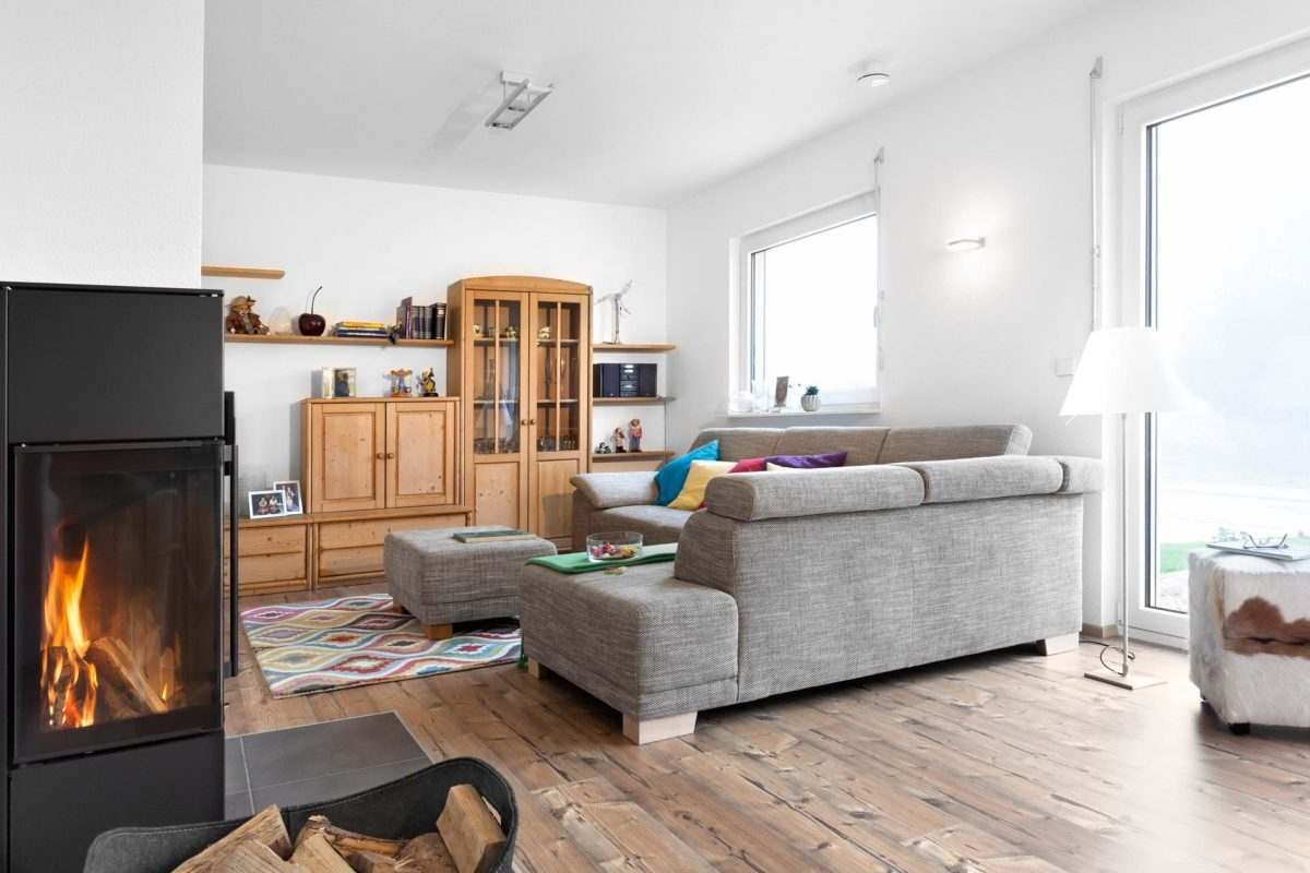 Haus Noller - Ein Kamin in einem Wohnzimmer mit Möbeln und einem Kamin - SchworerHaus KG