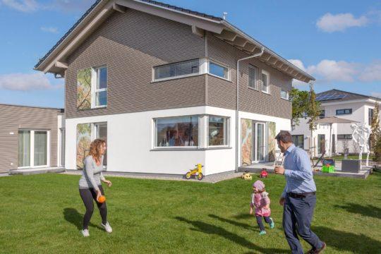 Musterhaus Günzburg - Eine Gruppe von Menschen, die Frisbee in einem Garten spielen - Haus