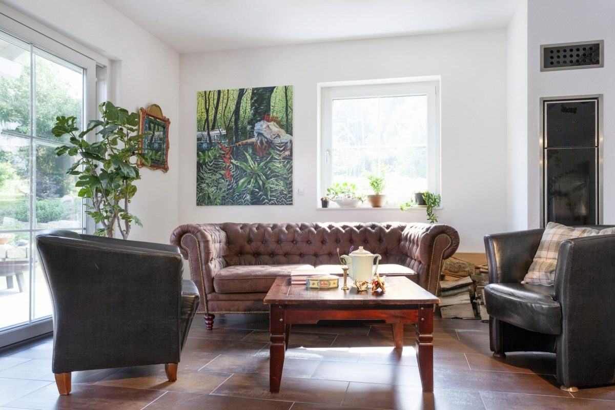 Haus Hälker - Ein Wohnzimmer mit Möbeln und einem Kamin - Fertighaus