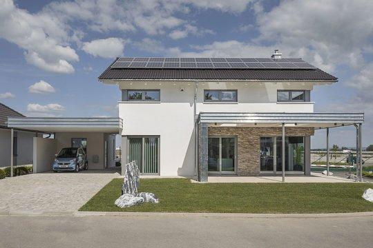 Musterhaus Lanos Wien - Ein großes Backsteingebäude mit Gras vor einem Haus - Haus