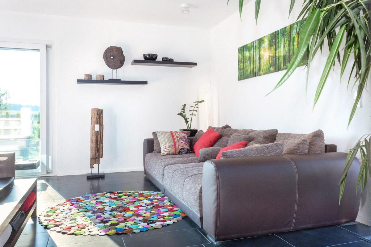 Haus Triebner - Ein Wohnzimmer mit Möbeln und einem Flachbildfernseher - Fertighaus