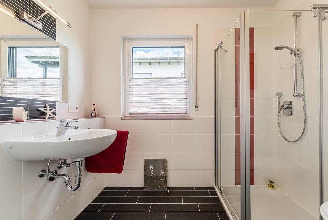 Kundenhaus Linz - Ein weißes Waschbecken sitzt unter einem Fenster - Bad