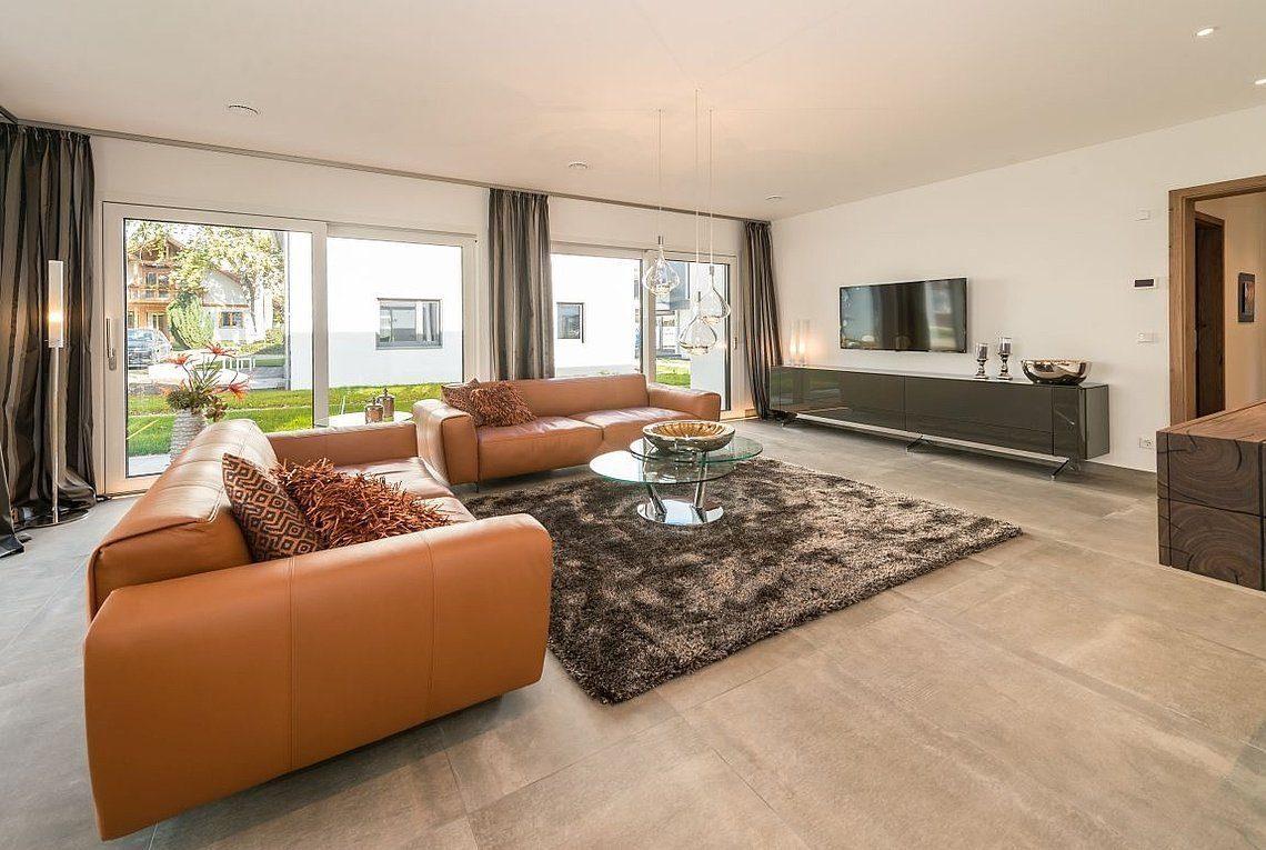 Musterhaus San Diego - Ein Wohnzimmer mit Möbeln und einem großen Fenster - Haus