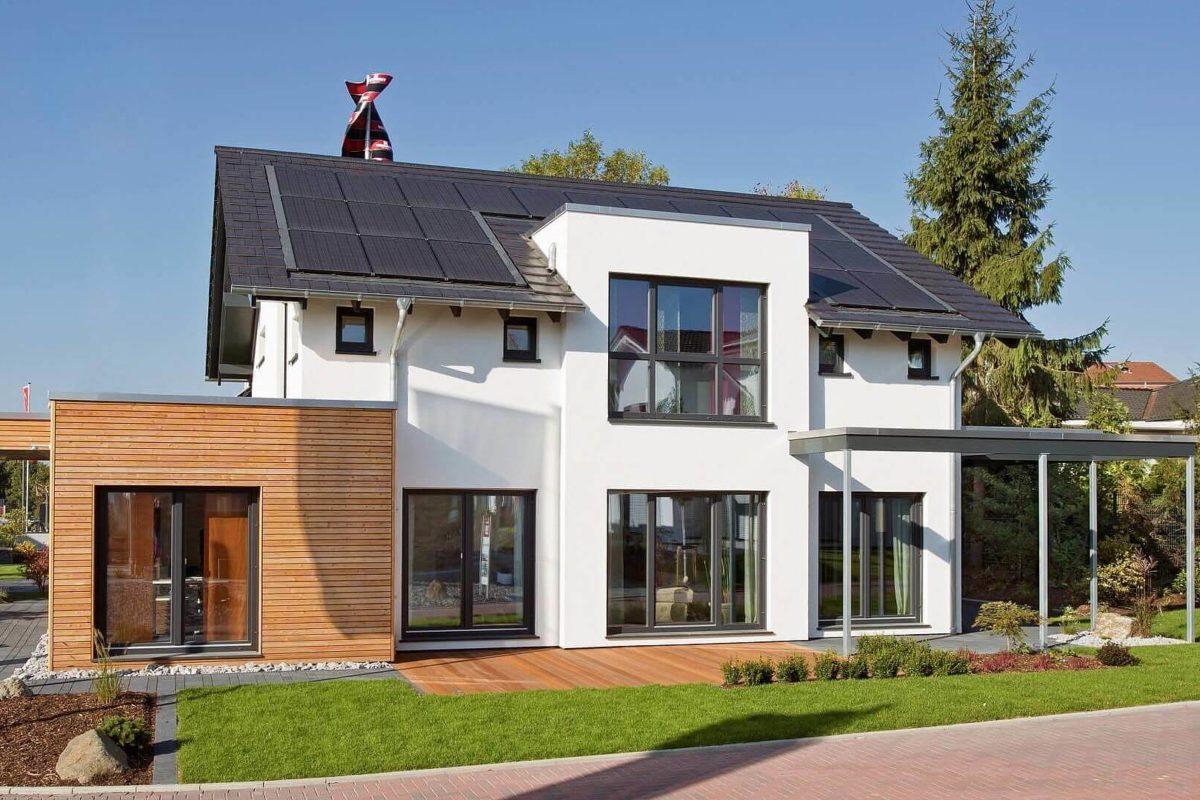 Musterhaus Wuppertal - Ein großes Backsteingebäude mit Gras vor einem Haus - Fertighaus
