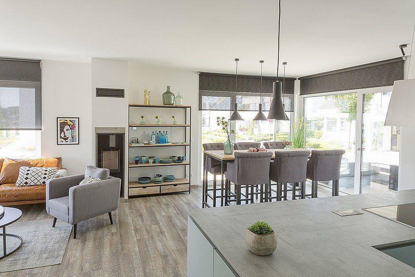 Musterhaus Lanos Wien - Ein Wohnzimmer mit Möbeln und einem großen Fenster - Interior Design Services