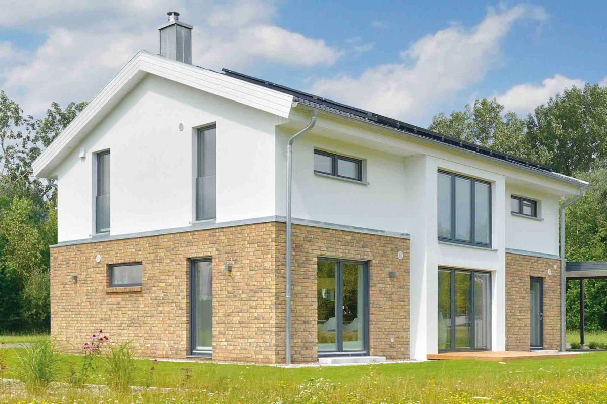 Musterhaus Kronhagen - Ein großes Backsteingebäude mit Gras vor einem Haus - Danhaus GmbH