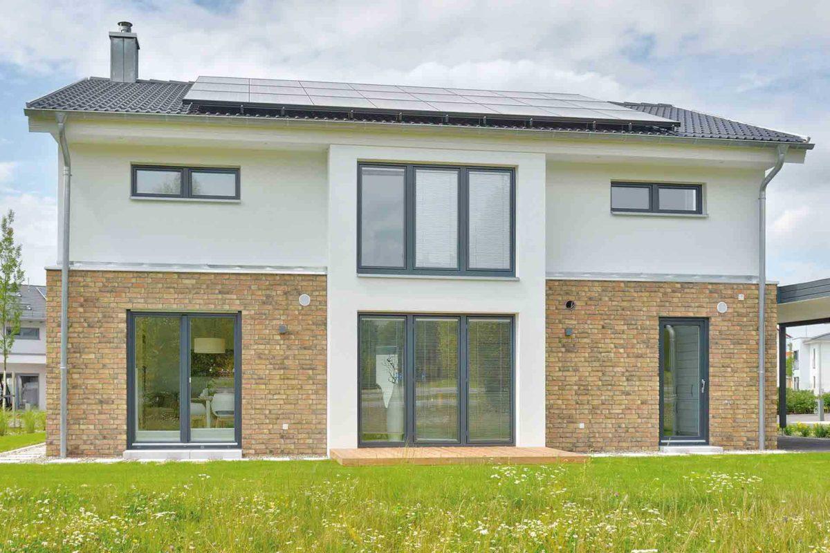 Musterhaus Kronhagen - Ein großes Backsteingebäude mit Gras vor einem Haus - Haus