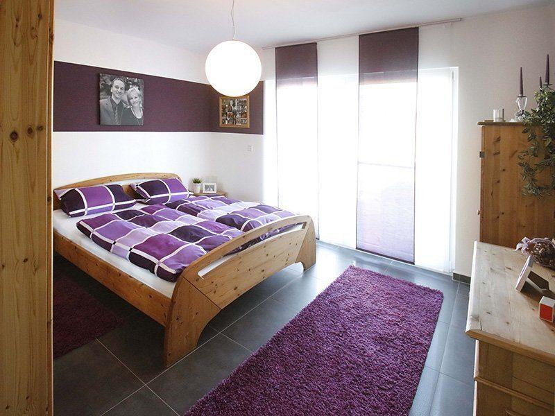 FAMILY 112 - Ein Schlafzimmer mit einer lila Decke auf einem Bett - Bettrahmen