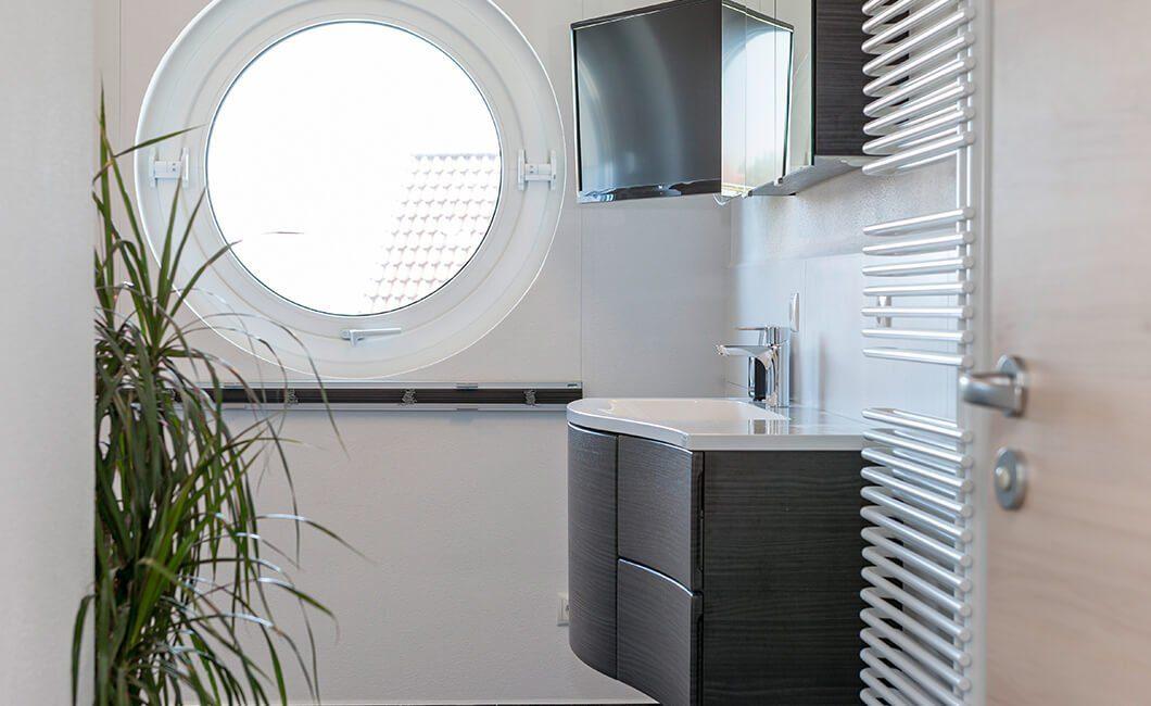 Edition 170 - Ein weißes Waschbecken sitzt unter einem Fenster - Haus