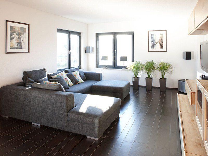 AT– Freiraum zum Wohlfühlen - Ein Wohnzimmer mit Möbeln und einem großen Fenster - Bauhaus