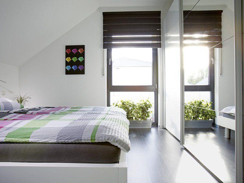 Ein Haus zum Wohlfühlen - Ein Schlafzimmer mit einem großen Fenster - FingerHaus