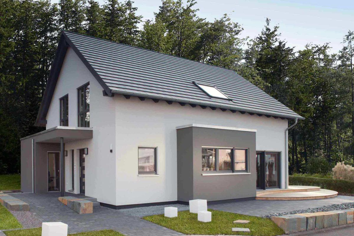 NEO 312 – Musterhaus Bad Vilbel - Ein großes Backsteingebäude mit Gras vor einem Haus - FingerHaus
