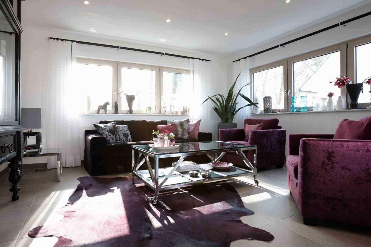 NEO 312 – Musterhaus Bad Vilbel - Ein Wohnzimmer mit Möbeln und einem großen Fenster - FingerHaus