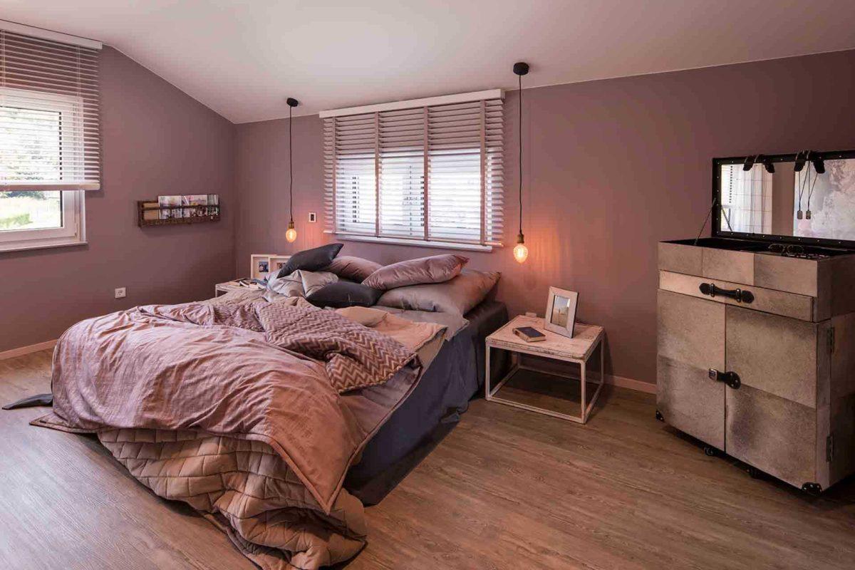 Musterhaus Sento 500 B - Ein Schlafzimmer mit einem Bett und einem Schreibtisch in einem Raum - FingerHaus