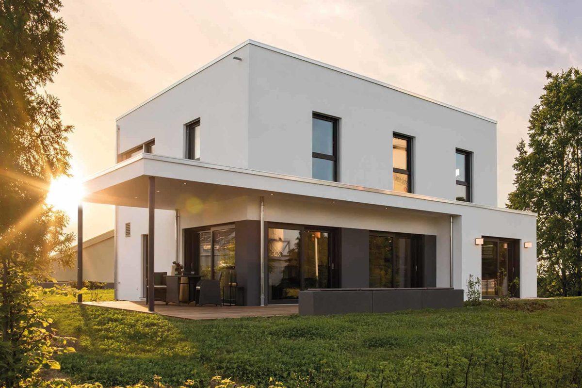 Musterhaus Gießen – Maxim - Ein großes Backsteingebäude mit Gras vor einem Haus - Bauplanung Sven Jäger