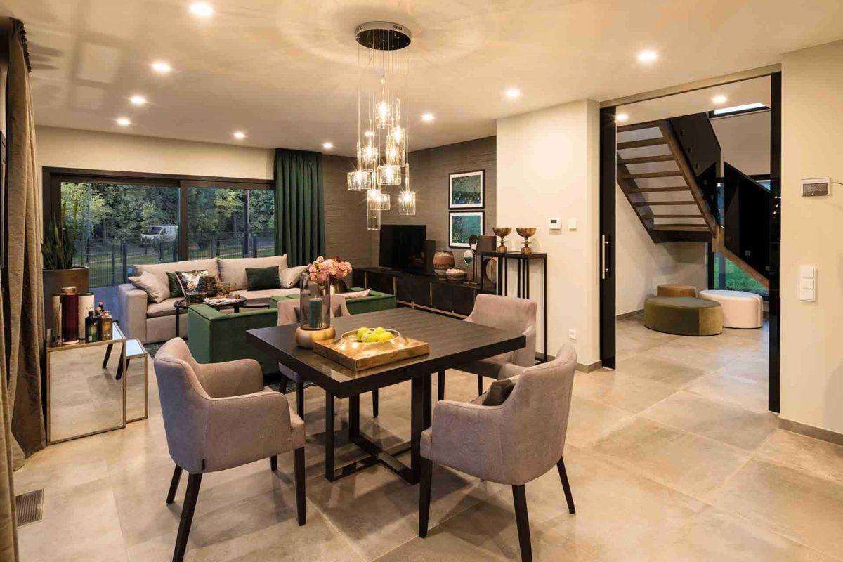 Musterhaus Gießen – Maxim - Ein Wohnzimmer mit Möbeln und einem großen Fenster - FingerHaus
