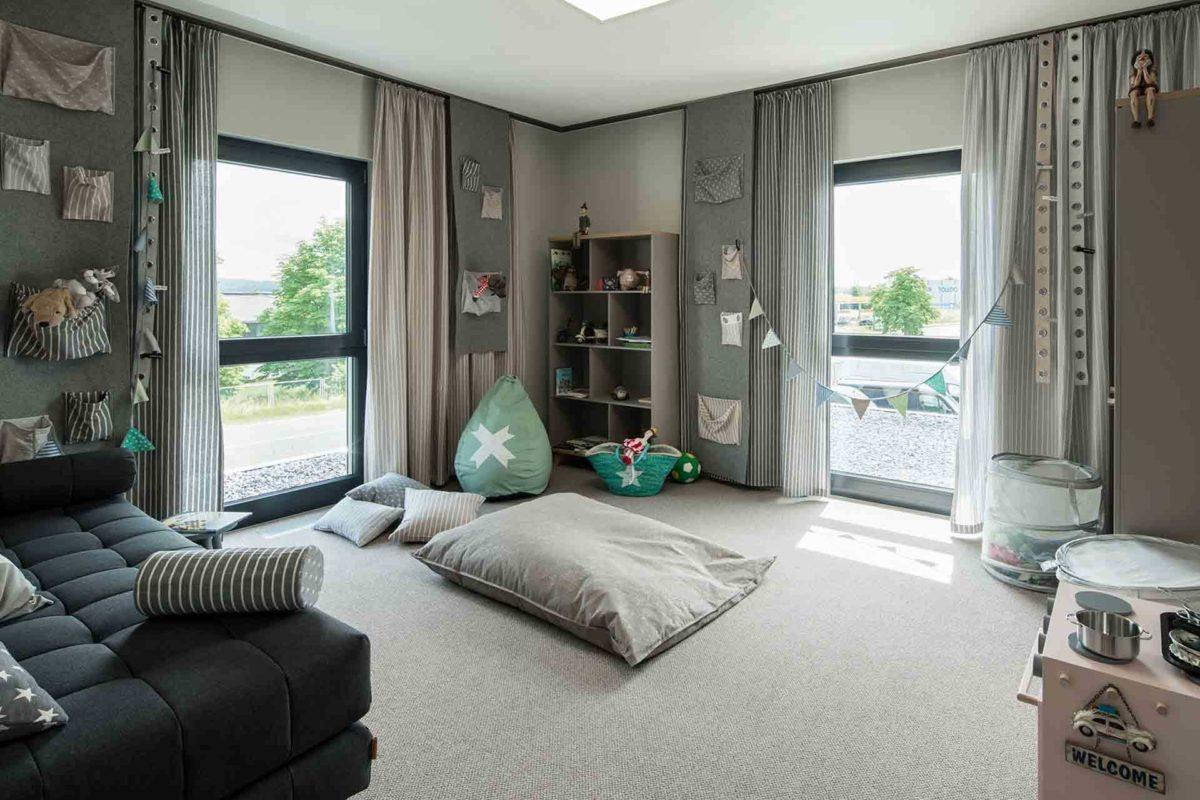 Musterhaus Gießen – Maxim - Eine Ansicht eines mit Möbeln gefüllten Wohnzimmers und eines großen Fensters - FingerHaus