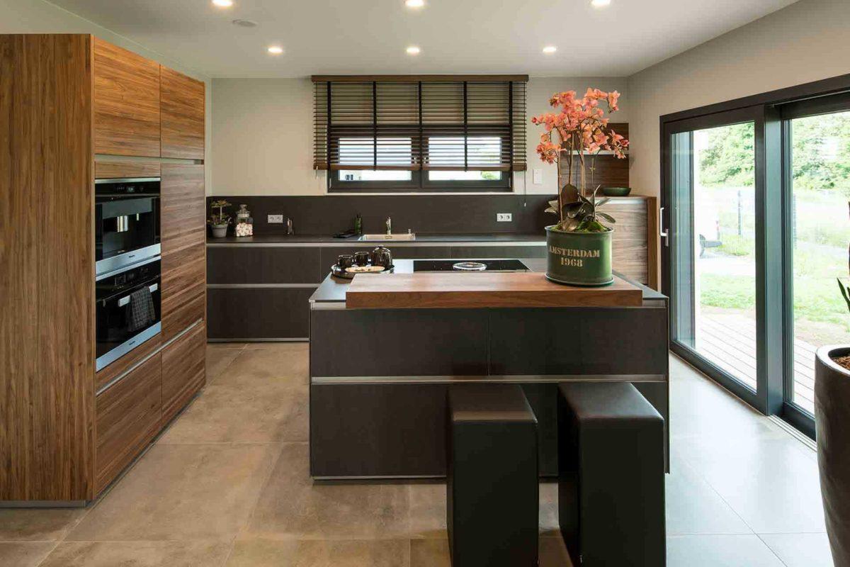 Musterhaus Gießen – Maxim - Eine moderne Küche mit einer Insel mitten in einem Raum - Küche